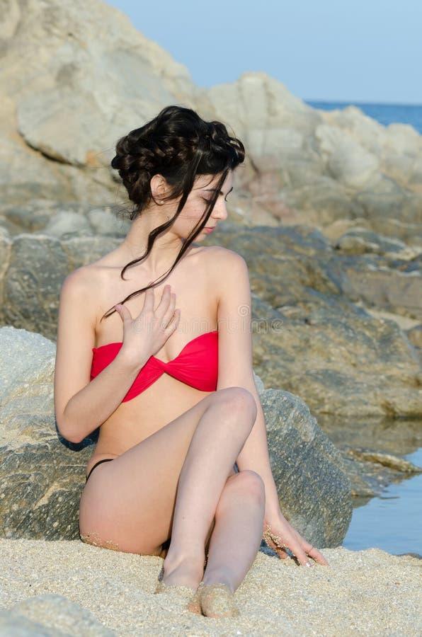 Barnet bantar nätt rött och svart bikinisammanträde för damkläder på sand royaltyfri bild