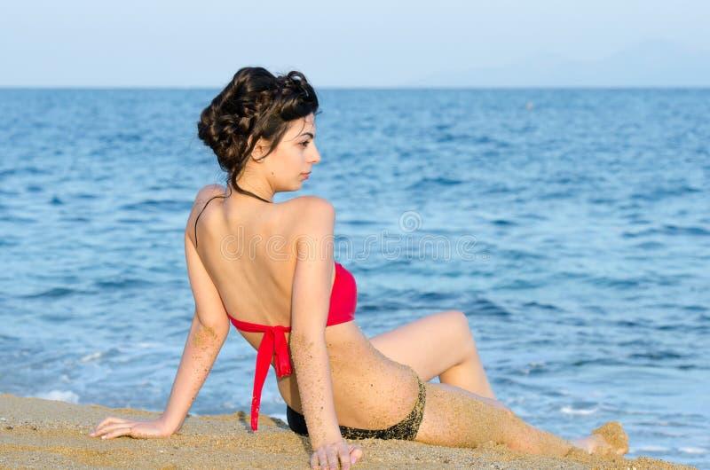 Barnet bantar nätt sammanträde för damkläderbikini på sand och stirrar havssikten royaltyfria bilder
