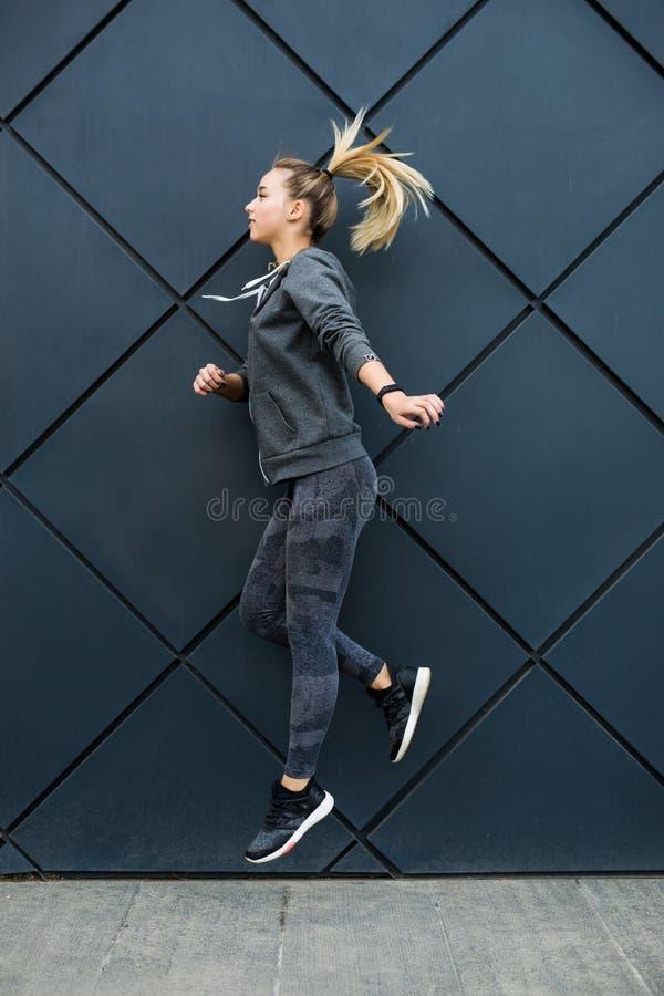 Barnet bantar sportkvinnan i konditionklädbanhoppning och rinnande det fria på väggbakgrund royaltyfria bilder