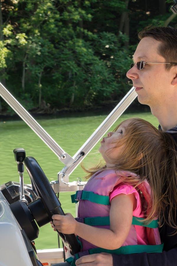 Barnet behandla som ett barn flickan eller lilla barnet som kör hastighetsfartyget med fadern arkivfoto