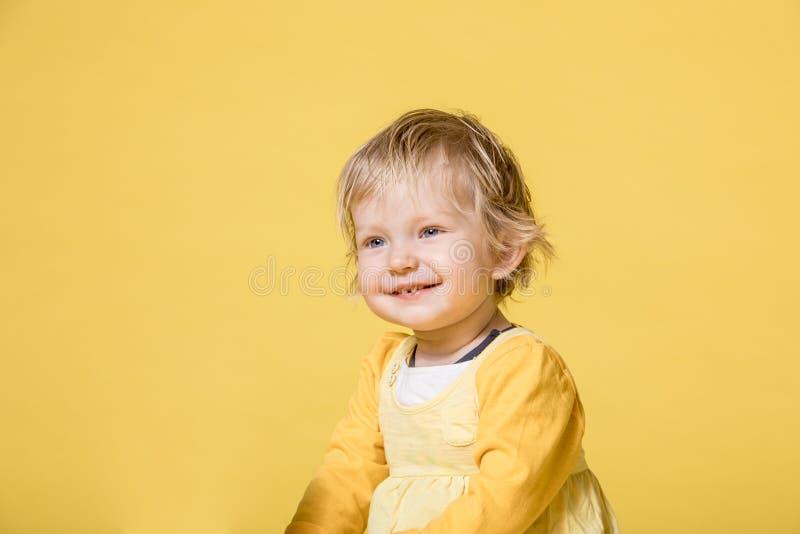 Barnet behandla som ett barn flickan i gul kl?nning p? gul bakgrund arkivfoto