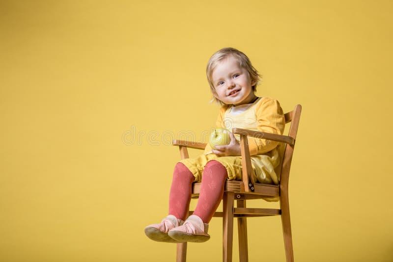 Barnet behandla som ett barn flickan i gul kl?nning p? gul bakgrund royaltyfria bilder