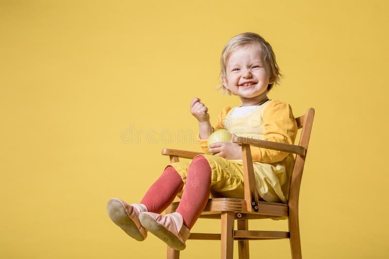 Barnet behandla som ett barn flickan i gul kl?nning p? gul bakgrund royaltyfri fotografi