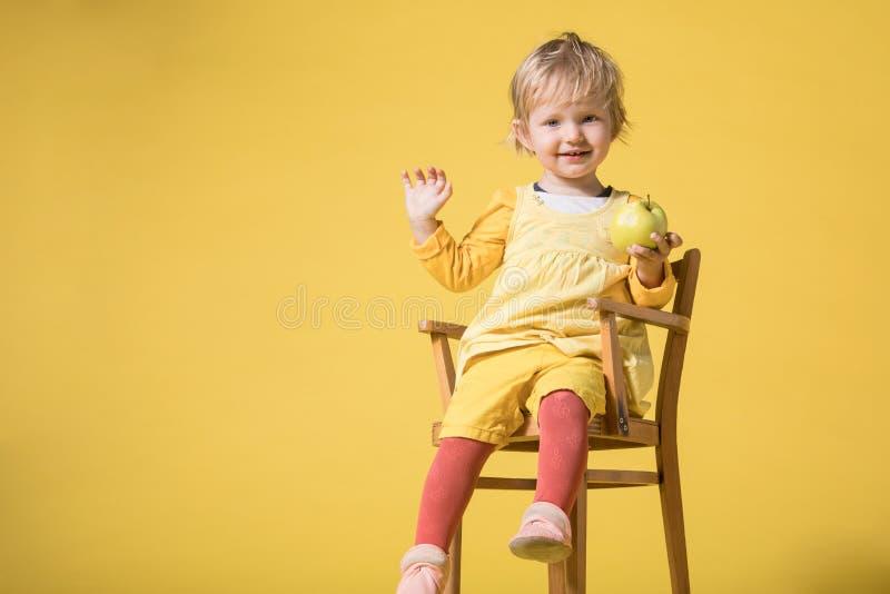 Barnet behandla som ett barn flickan i gul kl?nning p? gul bakgrund arkivbilder