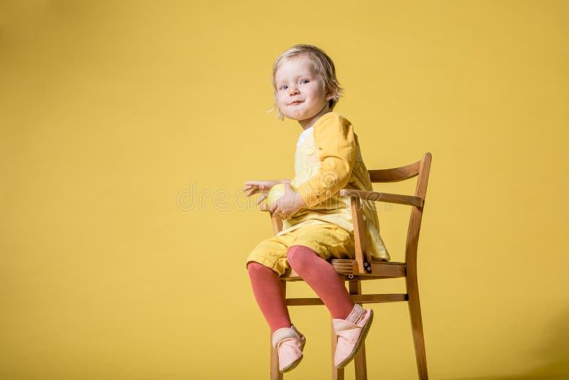 Barnet behandla som ett barn flickan i gul kl?nning p? gul bakgrund royaltyfri foto