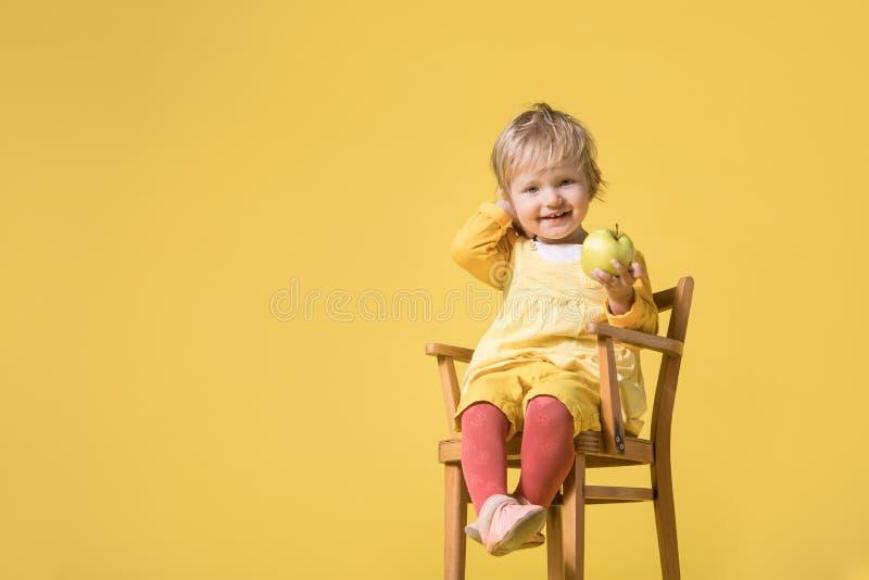 Barnet behandla som ett barn flickan i gul kl?nning p? gul bakgrund arkivfoton