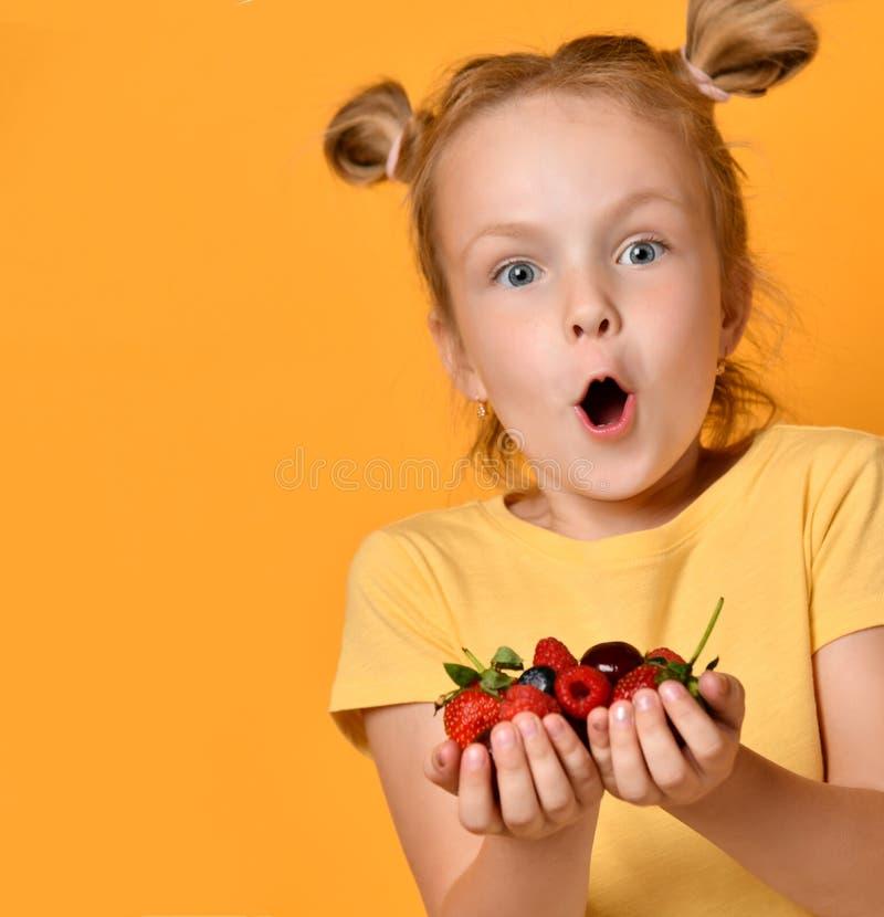 Barnet behandla som ett barn flickaungen, hållbär somfrukter i händer förvånade lyckligt skratta skrika på guling royaltyfri fotografi