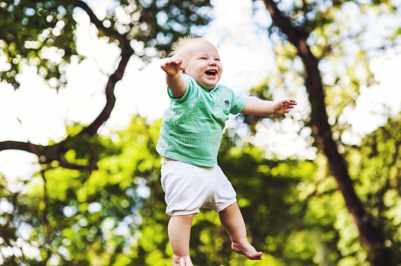Barnet behandla som ett barn pojkebanhoppning i midair arkivbild