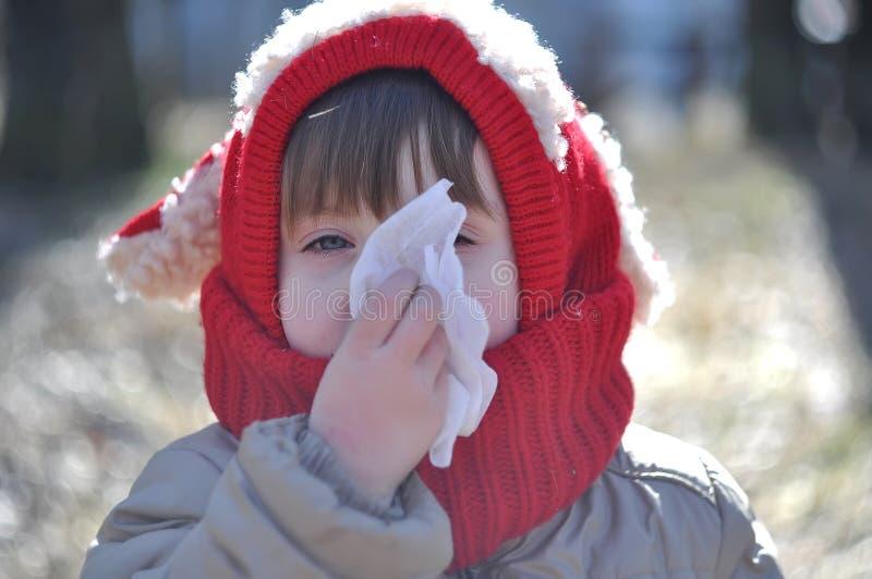 Barnet blåser hans näsa i en servett fotografering för bildbyråer