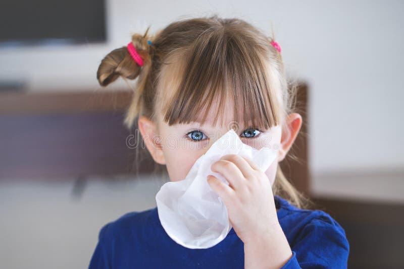 Barnet blåser hennes näsa in i en näsduk arkivfoton