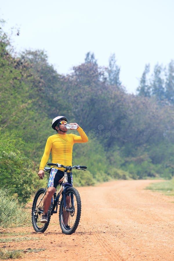 Barnet cyklar mannen (för cyklisten som) dricker sötvatten från plast- bo arkivfoton