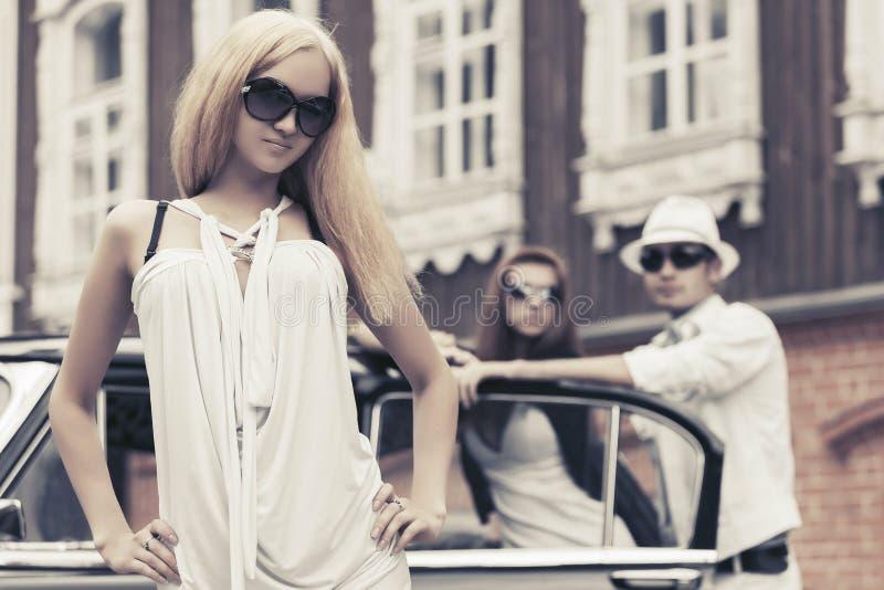 Barnet danar den blonda kvinnan i den vita klänningen bredvid den retro bilen arkivfoton