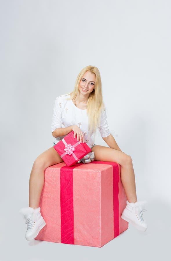 Barnet den gladlynta flickan sitter på en stor gåva, på vit backg royaltyfria bilder