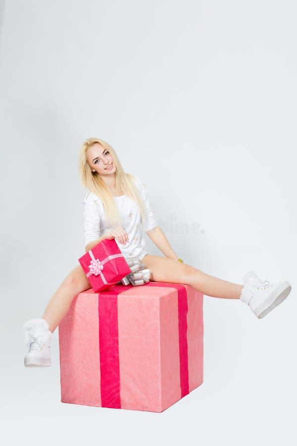 Barnet den gladlynta flickan sitter på en stor gåva, på vit backg royaltyfri fotografi