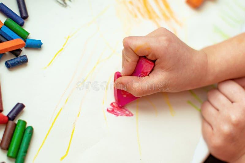 Barnet drar en blomma på papper med vaxfärgpennor som göras med hans egna händer royaltyfri fotografi