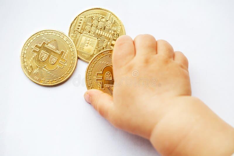 Barnet drar händer till Bitcoin cryptocurrencymynt Framtiden är decentraliserade system Närbild arkivbild