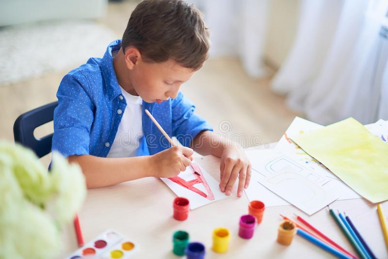 Barnet drar med en borstevattenfärg målar på papper bokstaven A arkivfoton