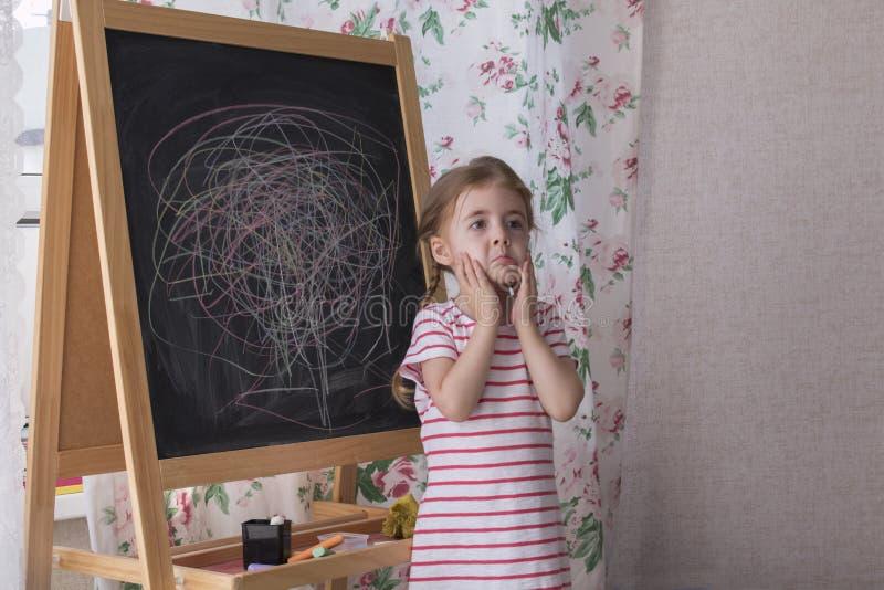Barnet drar med stycken av färgkrita på kritabrädet Flickan uttrycker kreativitet och ser kameran royaltyfria foton