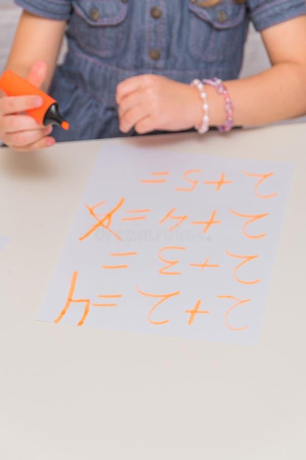 Barnet en flicka på tabellen skriver, drar på ett stycke av papper, mot en vit tegelstenvägg arkivbilder