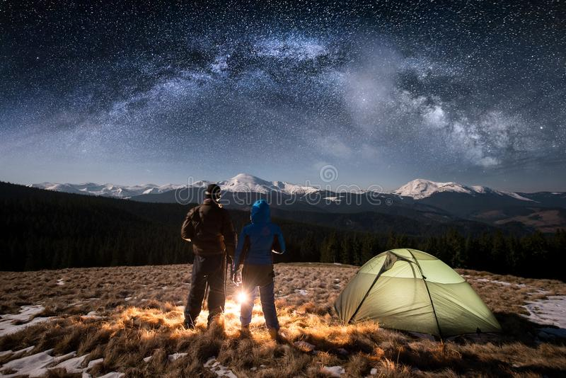 Barnet för bakre sikt kopplar ihop turister som har en vila i campa på nigh under natthimmel mycket av stjärnor och den mjölkakti royaltyfri bild