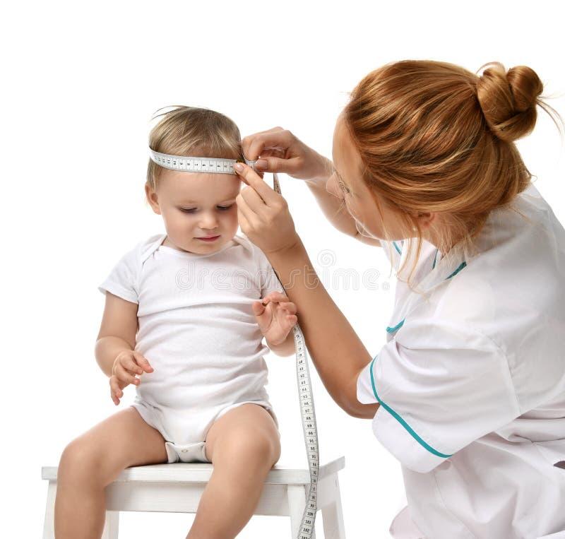 Barnet för det pediatriska måttet för doktorer behandla som ett barn det begynnande litet barnungehuvudet med måttband som isoler royaltyfria bilder