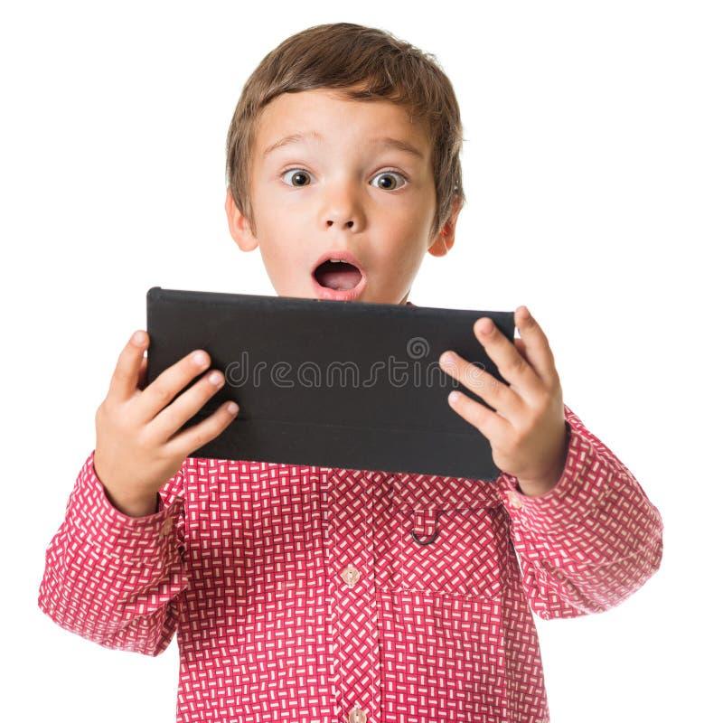 Barnet förvånade den hållande minnestavlan för pojken som ser skärm arkivbilder