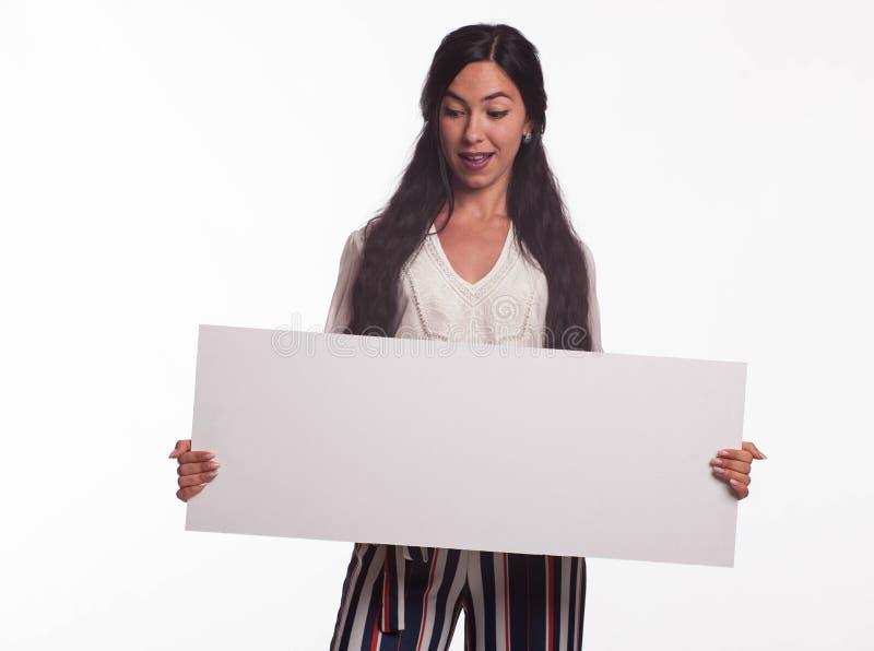 Barnet förvånade kvinnavisningpresentationen som pekar på plakat fotografering för bildbyråer