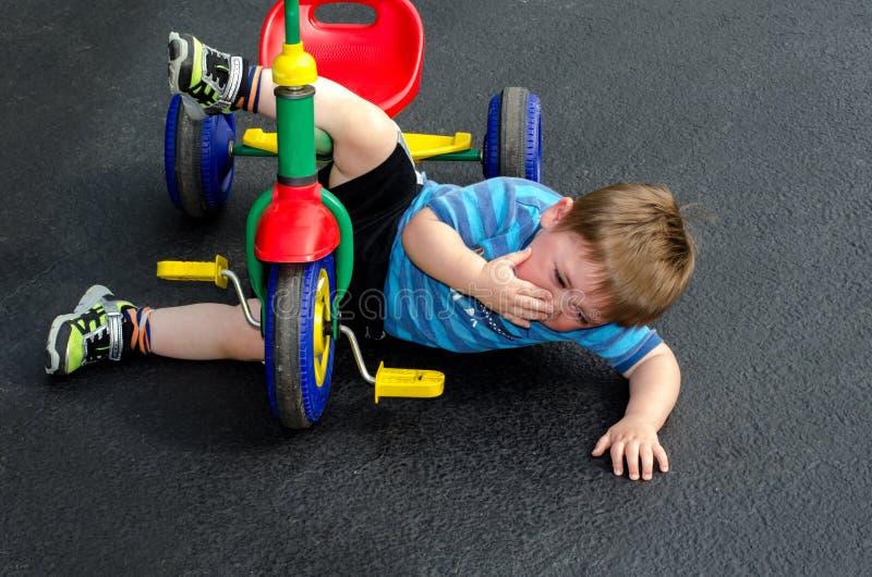 Barnet faller av trehjulingen royaltyfria foton