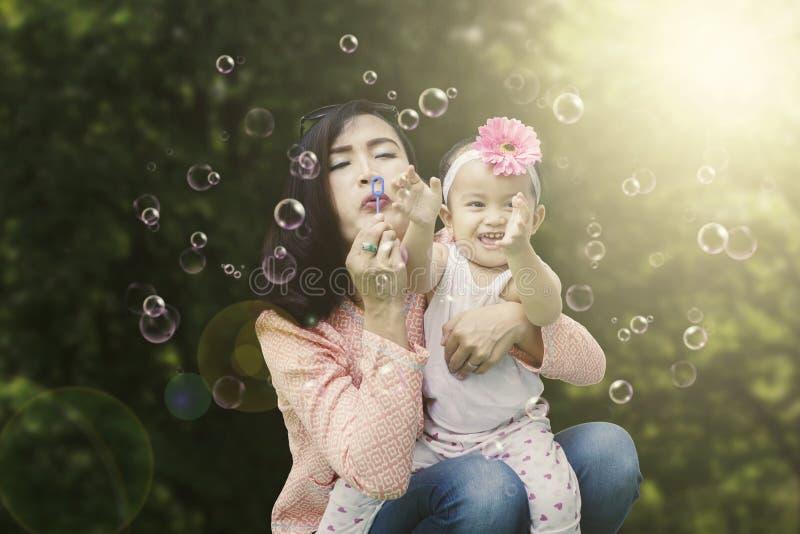 Barnet fostrar att blåsa såpbubblor arkivbild