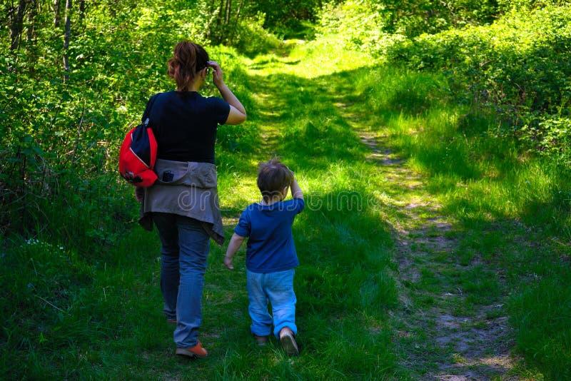 Barnet fostrar att gå med hennes lilla son utomhus i sommar arkivbilder