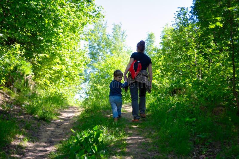 Barnet fostrar att gå med hennes lilla son utomhus i sommar royaltyfria bilder
