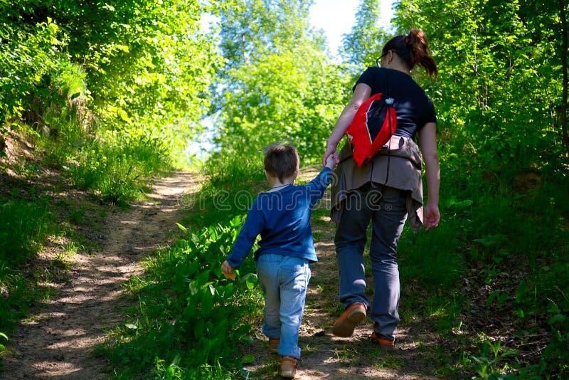 Barnet fostrar att gå med hennes lilla son utomhus i sommar arkivfoton