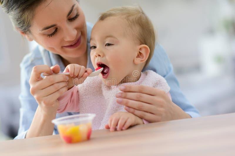 Barnet fostrar att ge fruktsallad till hennes behandla som ett barn flickan royaltyfria bilder