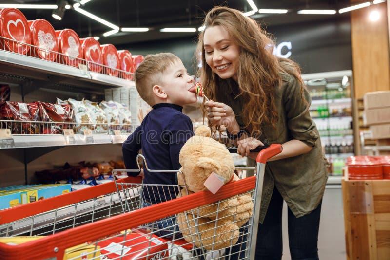 Barnet fostrar att ge godisen till hennes son royaltyfria bilder