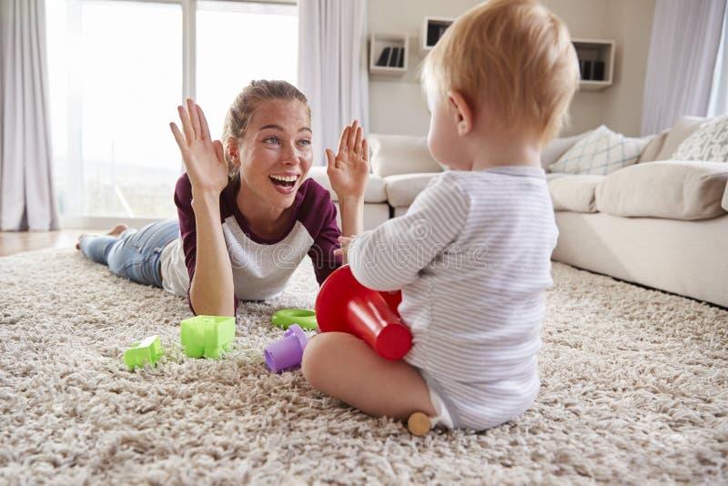 Barnet fostrar att ligga på golvet som hemma spelar med litet barnsonen fotografering för bildbyråer