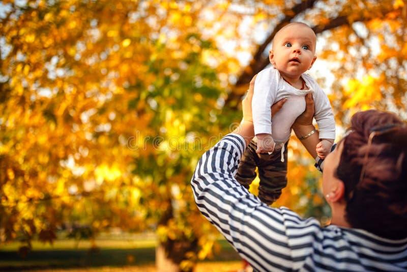 Barnet fostrar att spela med hennes litet behandla som ett barn sonen på solsken värme a royaltyfria bilder