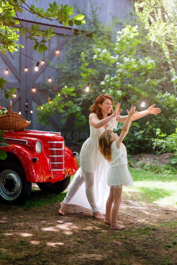 Barnet fostrar att spela, och ha gyckel med hennes lilla dotter i grön sommar parkera nära den röda retro bilen Familjlycka, barn royaltyfri fotografi