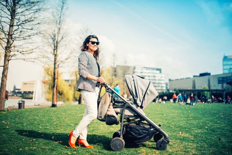 Barnet fostrar det bärande barnet i pram Fostra att gå in parkerar med nyfött och pramen royaltyfria bilder