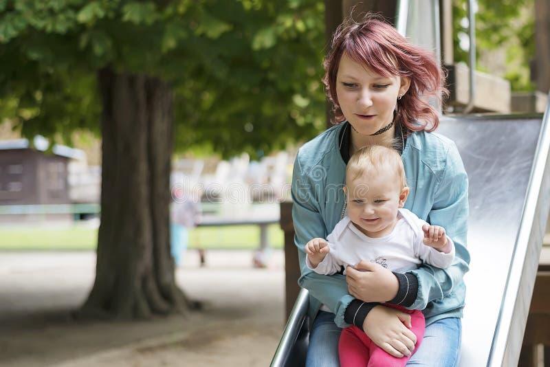 Barnet fostrar lyckligt att spendera tid med ett ungt barn i en sommar parkerar royaltyfri fotografi