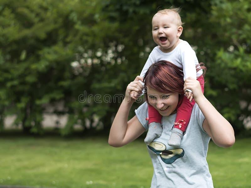 Barnet fostrar lyckligt att spendera tid med ett ungt barn i en sommar parkerar arkivbilder