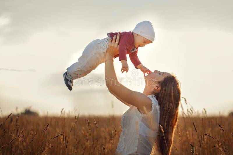 Barnet fostrar med hennes gulliga barn, moder som kast behandla som ett barn upp och att skratta och spela i sommaren på naturen royaltyfria foton