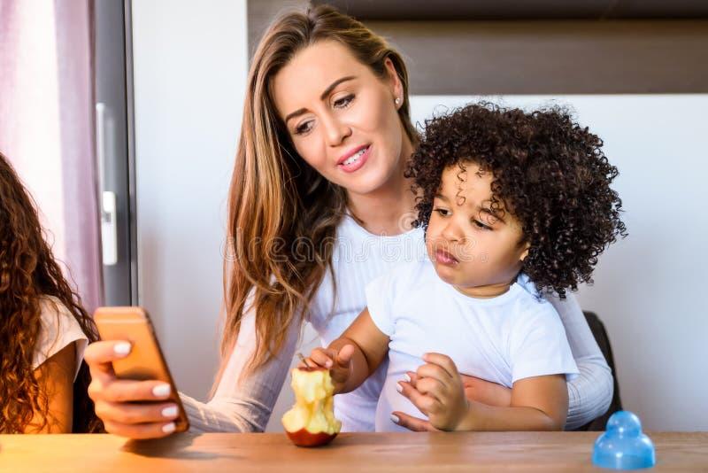 Barnet fostrar med hennes lilla pojke arkivfoton