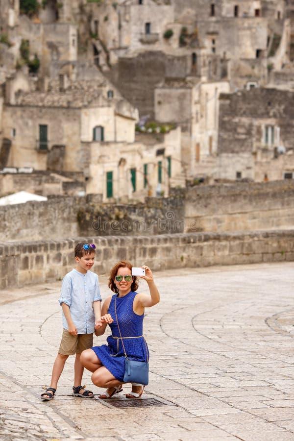 Barnet fostrar med hennes lilla son som utomhus går i stad och gör selfie royaltyfri fotografi
