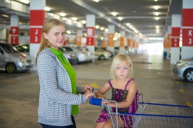 Barnet fostrar och den förtjusande dottern i shoppingvagn på undergrou royaltyfri foto
