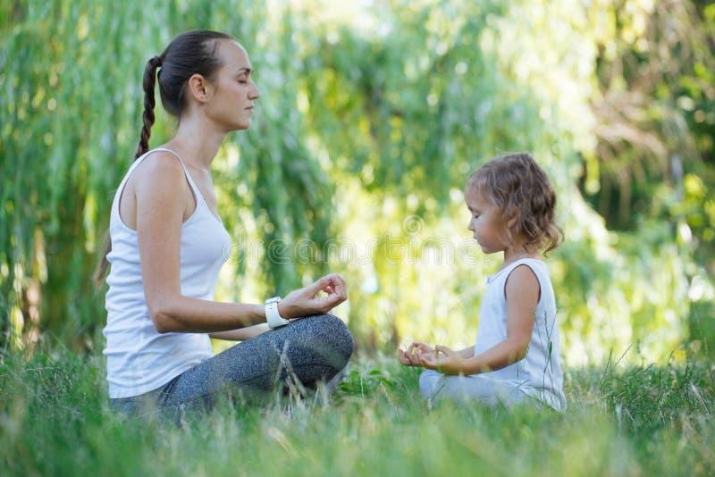 Barnet fostrar, och den gulliga lilla dottern som mediterar i lotusblomma, poserar tillsammans arkivfoton