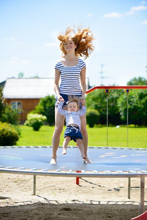 Barnet fostrar och den lilla dottern som studsar på trampolinen royaltyfri fotografi