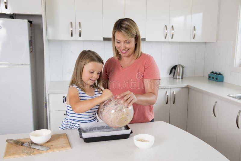 Barnet fostrar och den söta lilla dottern som tillsammans bakar lyckligt hemmastatt kök i familjlivsstilbegrepp royaltyfri fotografi