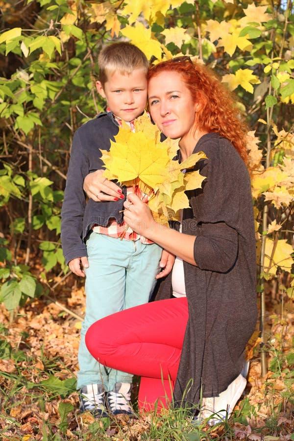 Barnet fostrar och den stiliga lilla sonen med gula lönnar royaltyfri fotografi