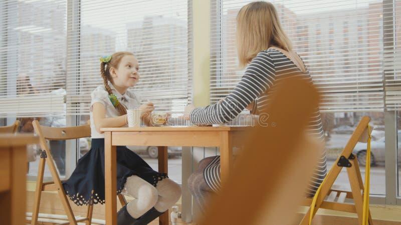 Barnet fostrar, och dottern äter caks och dricker på bagerit arkivfoton