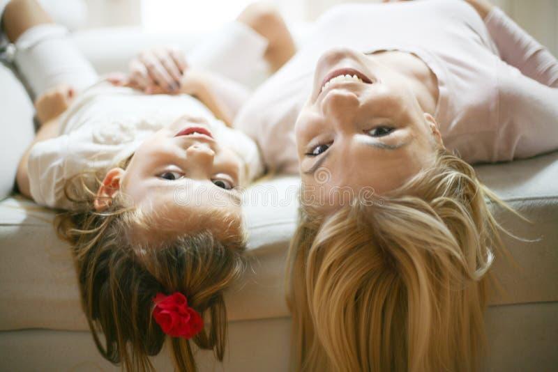 Barnet fostrar och dottern på säng royaltyfri foto